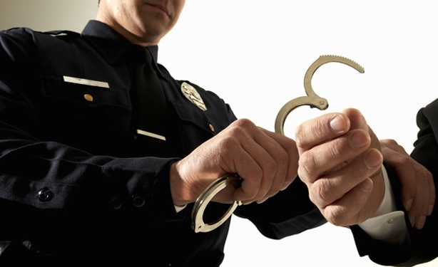 Male police officer handcuffing businessman