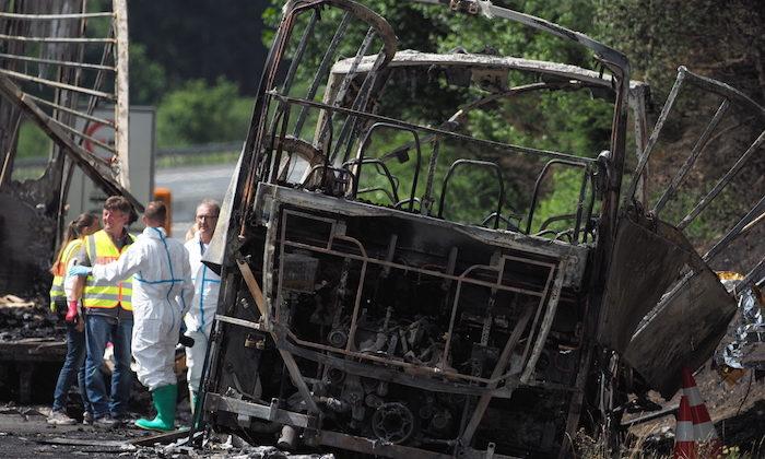 Bomberos y rescatistas trabajan junto a un autobús quemado en la autopista A9 cerca de Muenchberg, Alemania, el lunes 3 de julio de 2017 después de que el vehículo chocara con un camión y se incendiara. (Nicolas Armer/dpa vía AP)